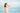 Frau steht mit geschlossenen Augen am Meer und laesst sich die Brise durch die Haare fahren