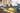 Gelbes Coenzym Q10-Pulver mit lavera Cremetiegel und Make up Produkten im Hintergrund auf schwarzem Tisch
