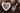 Weiße Porzellanschale in Herzform gefüllt mit dunklen Chiasamen und kleiner silberfarbener Löffel mit Chiasamen auf dunklem Holztisch