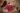 Umgefallener geflochtener Korb gefüllt mit Cranberries die auf einen dunklen Holztisch rollen